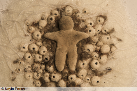 film frame from White Body depicts close-up image of small figure or doll (no features) sculpted from white modeling clay, lying in a bed of white crystals (granulated sugar), white sewing thread, and tiny round white eggs/beads, infiltrated with grey-brown dusty fluff (slut's wool)