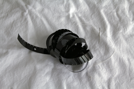 Colour photograph is of a length of black 16mm film, single perf, exposed to no light and processed, unraveling from the core, with a sewing needle threaded with white cotton; against a background of a white cotton sheet.